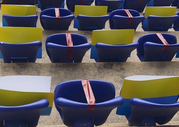 Zitplaatsen in een voetbalstadion tijdens een pandemie door middel van een geplakt om afstand te houden tijdens een wedstrijd.
