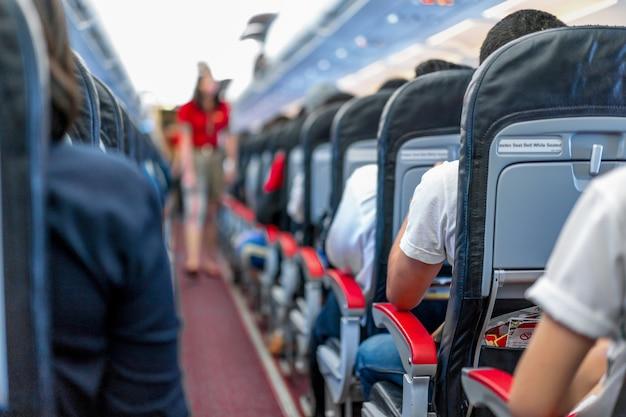 Zitplaatsen in het vliegtuig en passagiers zitten in het hele gebied te wachten op het vliegtuig dat van de startbaan opstijgt.