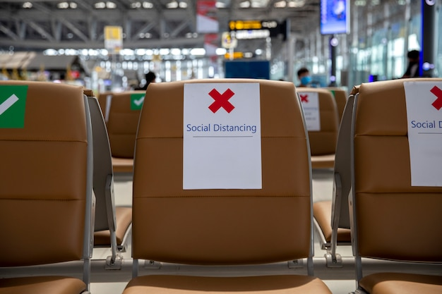 Zitplaatsen op de luchthaven met sociale afstandsborden