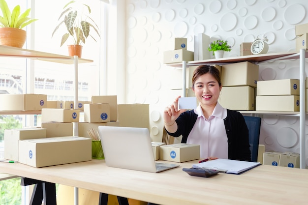 Zitten de levensstijl bedrijfsvrouwen die in bureau zitten witte kaartglimlach die, mkb-kleine onderneming werken