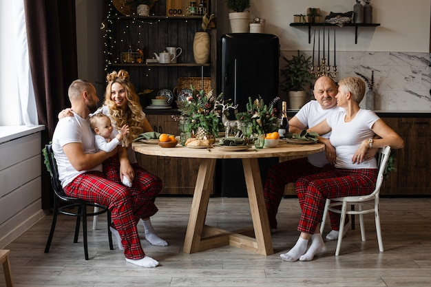 Zittend aan de feesttafel op kerstavond en gelukkige familie