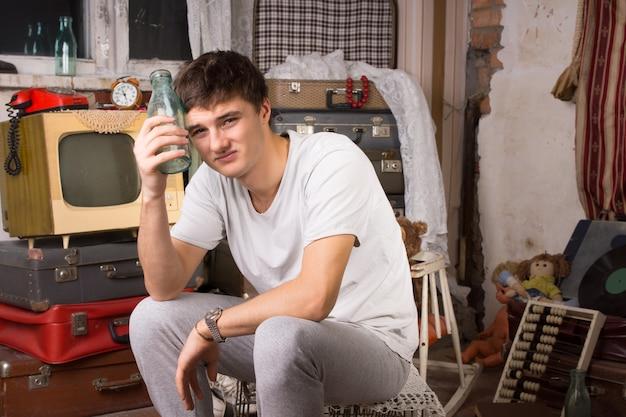 Zittend dronken jongeman in casual kleding met glazen fles in de rommelkamer terwijl hij naar de camera kijkt