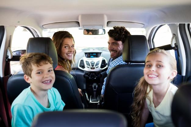 Zittend in de auto en gelukkige familie