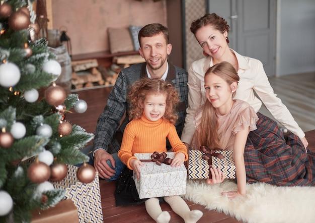 Zittend in de buurt van de kerstboom in de gezellige woonkamer en gelukkige familie.