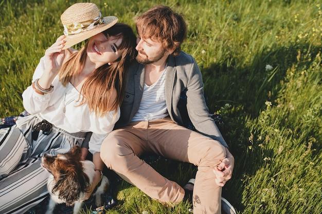 Zittend in gras jonge stijlvolle hipster paar verliefd wandelen met hond in platteland, zomer stijl boho mode, romantisch