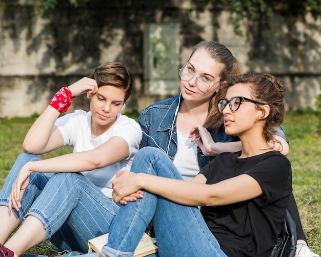 Zittend in park rusten vrouwelijke vrienden