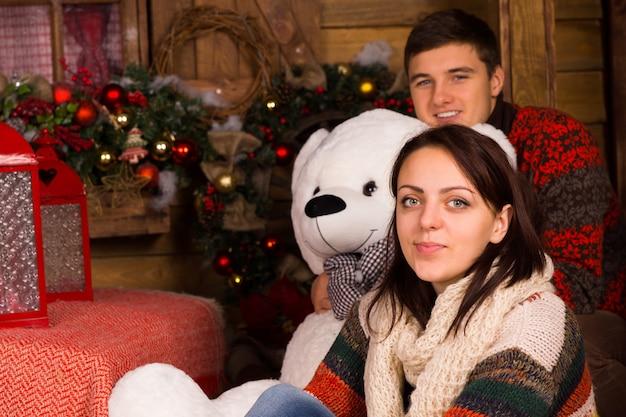 Zittend jong stel dat winteroutfits draagt met een grote witte beerpop terwijl ze naar de camera kijken.