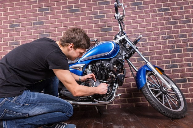 Zittend jonge knappe kerel in casual outfit zijn blauwe motorfiets handmatig repareren voor huis bakstenen muur