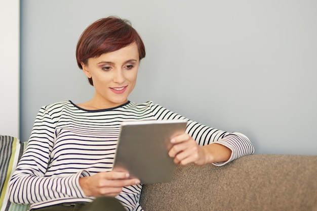 Zittend op de bank en browsen op digitale tablet