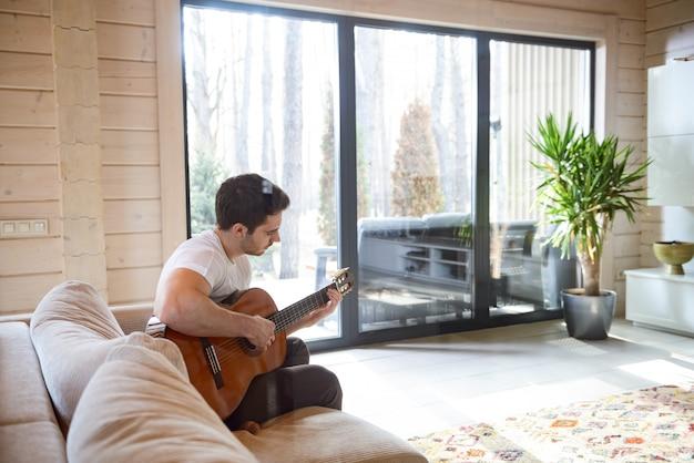 Zittend op de bank en gitaar spelen
