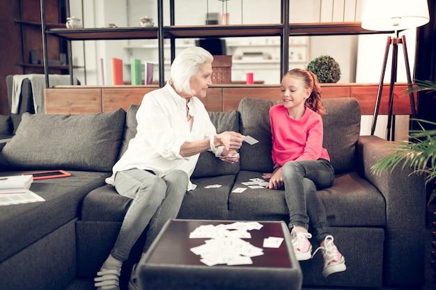 Zittend op de bank. oma en meisje zitten op de bank in de woonkamer en studeren met flashcards