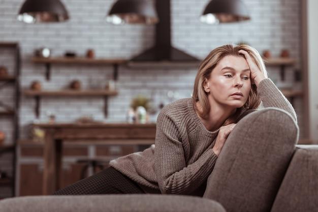 Zittend op de bank. rijpe familievrouw die op de bank in de woonkamer zit en zich gestrest voelt