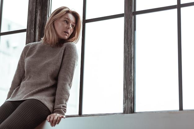 Zittend op de drempel. blondharige vrouw met een bruine trui die thuis op de vensterbank zit
