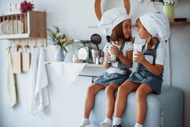 Zittend op de koelkast. familie kinderen in witte chef-kok uniform eten eten in de keuken.
