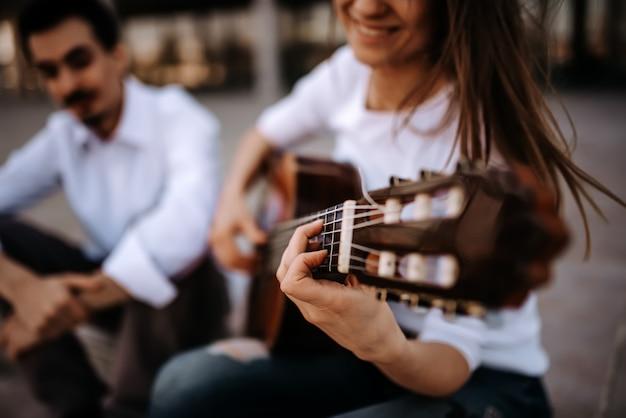 Zittend op de trap en gitaar spelen. meisje gitaarspelen terwijl het zitten met haar mannelijke vriend in openlucht in de stad.