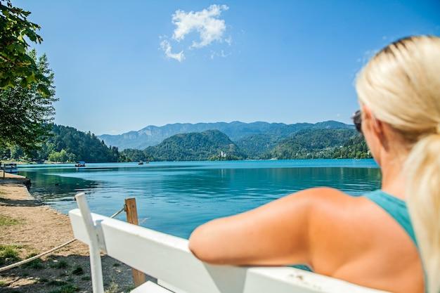 Zittend op een witte bank en kijkend naar het water