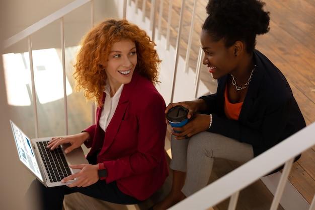 Zittend op trappen. twee arbeiders die op de trap zitten terwijl ze aan een laptop werken en koffie drinken