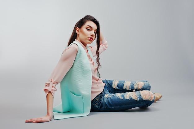 Zittend portret jong donkerbruin meisje die in roze blouse, turkoois jasje, gescheurde jeans en roomschoenen op grijze achtergrond dragen