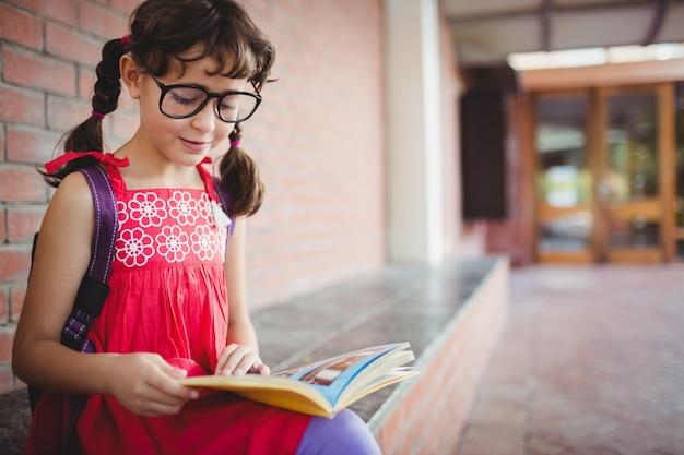 Zittend schoolmeisje dat een boek leest