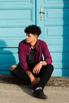 Zittende etnische tiener in geruit overhemd op rand