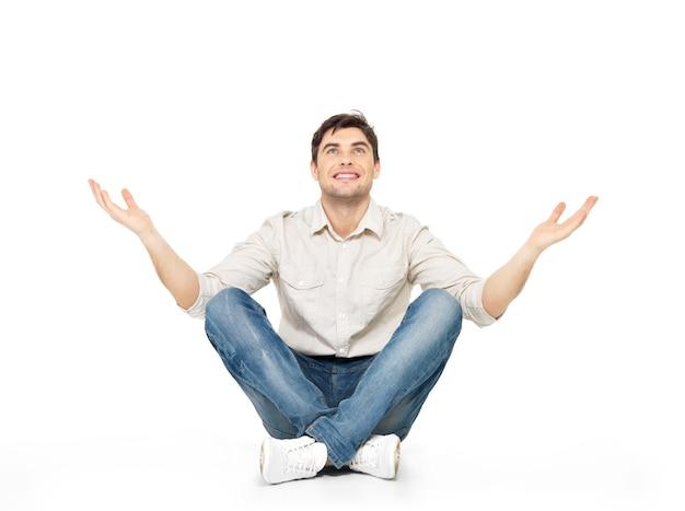 Zittende gelukkig man met opgeheven handen omhoog geïsoleerd op wit.