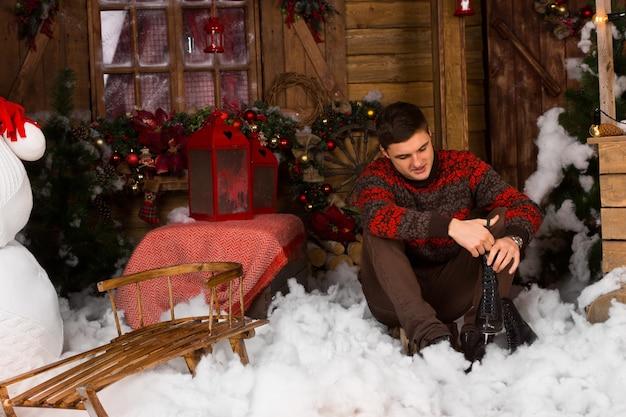 Zittende jonge knappe man met schaatsen met serieuze gezichtsuitdrukking, omringd door prachtige kerstdecors.