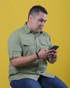 Zittende man die mobiele telefoon controleert