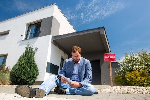 Zittende man zonder werk voor het huis tijdens economische crisis, onroerend goed verkopen