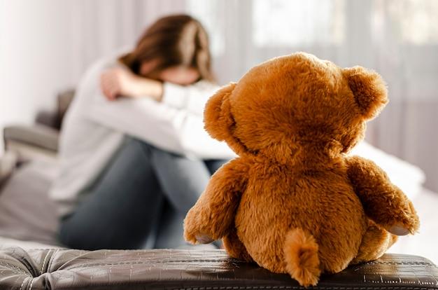 Zittende verstoorde vrouw en teddybeer. selectieve aandacht. verdeel concept