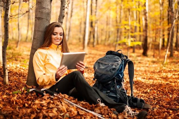 Zittende vrouwelijke wandelaar met behulp van digitale tablet