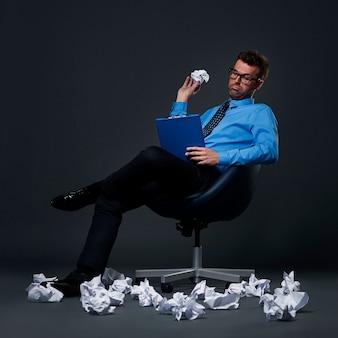 Zittende zakenman die een verfrommeld document met slechte ideeën over de vloer gooit