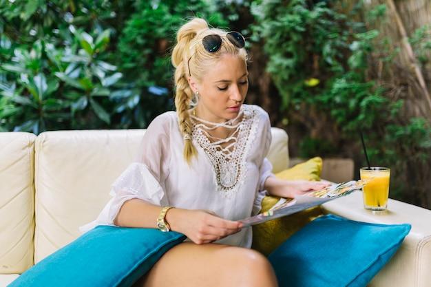 Zitting van de blonde de jonge vrouw op bank die menu bekijkt