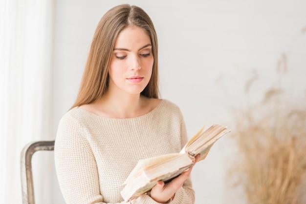 Zitting van de blonde de jonge vrouw op het boek van de stoellezing