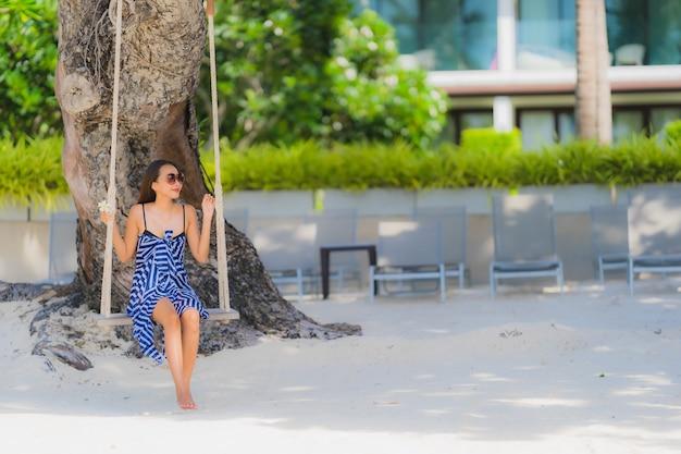 Zitting van de portret de jonge aziatische vrouw op schommelingskabel en overzees rond strand overzeese oceaankokosnotenpalm