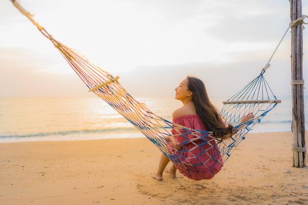 Zitting van de portret de mooie jonge aziatische vrouw op de hangmat met het strandoverzees en oce van glimlach gelukkige neary