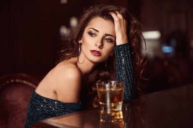 Zitting van de schoonheids de jonge donkerbruine vrouw bij de bar