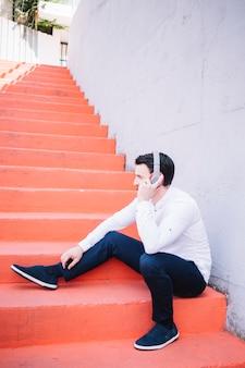 Zittingsmens die oortelefoons gebruikt