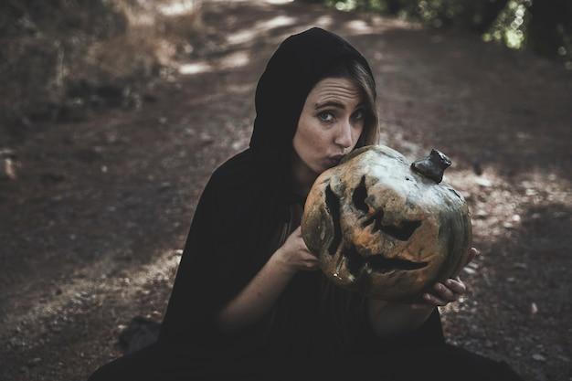 Zittingsvrouw in heksenkostuum die vreselijke pompoen kussen