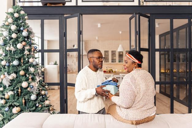 Zo aangenaam. opgetogen aardige vrouw die een geschenkdoos neemt terwijl ze wordt gefeliciteerd met kerstmis