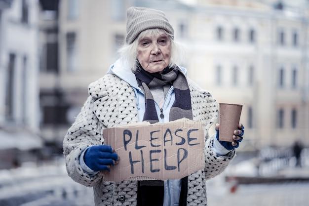 Zo arm. trieste oude vrouw die op straat staat terwijl ze mensen om hulp vraagt