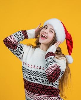 Zo blij. feest plezier. voorbereiden op de wintervakantie. gelukkig nieuwjaar. vrolijk kerstfeest. vrolijke tienermeisje viert kerstfeest. kind draagt rode kerstmuts. kind santa helper in gebreide trui.