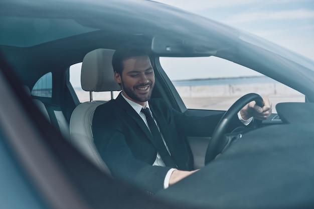 Zo blij! knappe jonge man in volledig pak glimlachend tijdens het autorijden