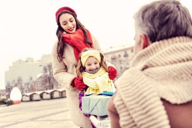 Zo blij. opgetogen jonge vrouw die glimlach op haar gezicht houdt en haar dochter omhelst