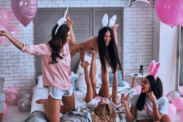 Zo blij! speelse jonge vrouwen in konijnenoren die plezier hebben en glimlachen terwijl ze genieten van een thuisfeest