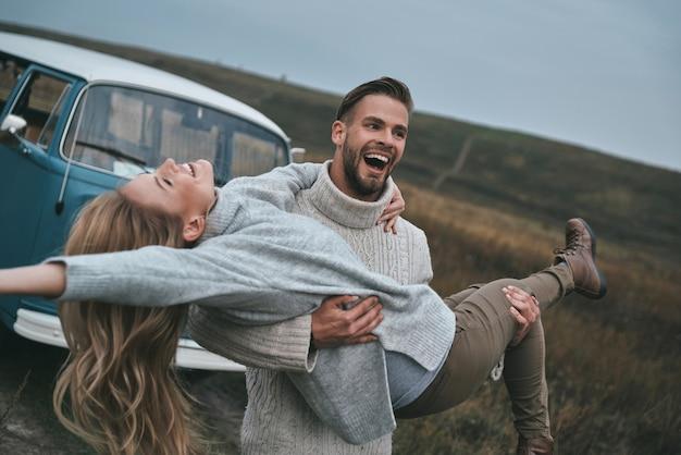 Zo blij voelen! knappe jonge man die zijn aantrekkelijke vriendin draagt en glimlacht terwijl hij buiten in de buurt van de blauwe retro-stijl minibus staat