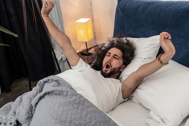 Zo comfortabel. aardige knappe man die in zijn comfortabele bed ligt terwijl hij probeert wakker te worden