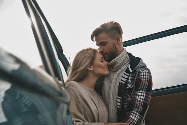 Zo fijn om samen te zijn. mooie jonge paar omhelzen en glimlachen terwijl ze buiten staan in de buurt van de retro-stijl minibus