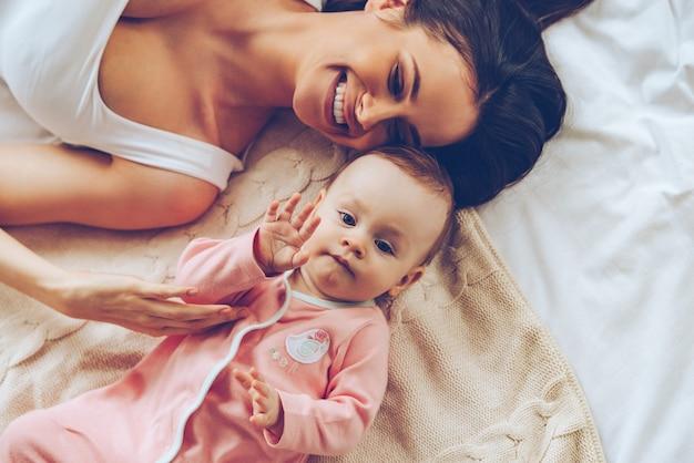 Zo fijn om wat langer in bed te blijven. bovenaanzicht van vrolijke mooie jonge vrouw die met haar babymeisje speelt terwijl ze in bed ligt