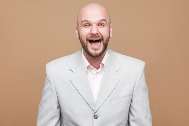 Zo grappig. portret van een vrolijke, knappe, kale, bebaarde zakenman van middelbare leeftijd in een klassiek lichtgrijs pak dat staat, kijkt en lacht om de camera. indoor studio opname, geïsoleerd op bruine achtergrond.