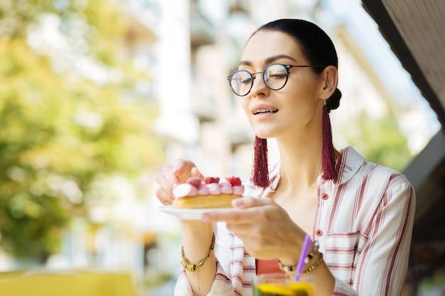 Zo heerlijk. mooie jonge persoon die een bril draagt en glimlacht terwijl hij naar de frambozen-eclair in haar handen kijkt
